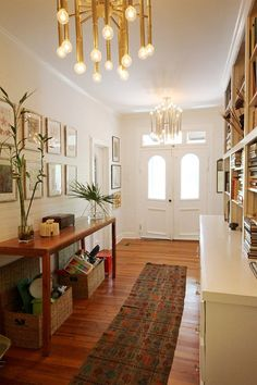 Perfect eclectic entryway including midcentury chandeliers, colonial doors, & warm woods