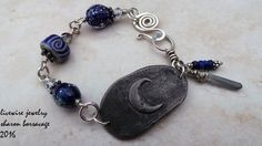 This very sparkly boho chic bracelet features a gorgeous pewter bar focal with a lovely raised moon design made by Inviciti Designs. The bracelet is linked together with stunning deep blue sparkly silver glass lampwork beads made byJulie Wong Sontag, and a wonderful ceramic swirl bead in blue made by Keith OConner. All the beads are accented with pewter spacers and czech glass beads, and all are linked with 18 gauge sterling silver. At the corner of the focal are 2 accent dangles of tiny…