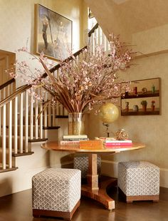 Make that stairway corner a functional space with a round entry table and elegant cubes. #foyer #entry