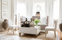 """""""When I painted this room, I'd fallen in love with Benjamin Moore's Linen White, and I loved how that looked with the white resin sculpture,"""" Tara says of the master bedroom's sitting area. Tara layered more white from there: drapes, a 22-ounce linen on the banquette, more Linen White in a high gloss on the coffee table."""