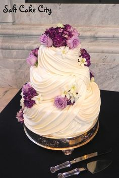 All marshmallow fondant  covered draping with purple flowers.