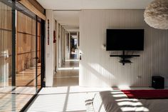 White-painted pine wood floors contrast the warmth of the exterior wood deck and extend throughout this main volume, which includes three bedrooms and bathrooms as well as storage arranged to the south. Pine Wood Flooring, Wood Walls, Dream Home Design, House Design, Glazed Walls, Steel Stairs, Modular Structure, Arch Interior, Japanese Architecture