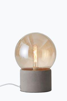 Bordlampe med fot av råbetong og ravfarget glasskuppel. Lampens høyde 21 cm. Ø glasskuppel 16 cm. Hvit tekstilledning med strømbryter, ledningslengde ca 175 cm. Liten sokkel E14. Maks 25 W.<br><br>Lyskilde inngår ikke. Ulike typer lyskilder kan ha stor innvirkning på stil og utseende hos lampen. Prøv deg fram til ditt eget uttrykk! <br><br>