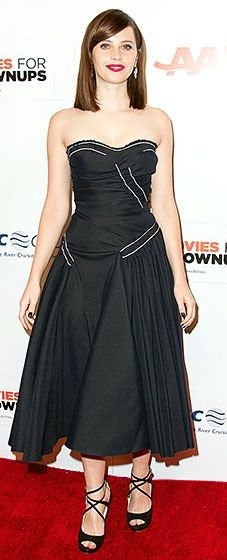 The Theory of Everything actress wore a Prada LBD with an asymmetrical skirt, strappy Jimmy Choo peep-toes, and a red statement lip.