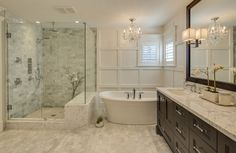 This beautiful contemporary master bathroom features an enormous vanity with white marble countertops and a large shower enclosure with a built in bench. Nestled between the two is the freestanding tub with a small chandelier hanging above it.