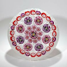 Parabelle Glass 1998 central mauve pansy paperweight, encircled by a ring of red bundled hearts, spaced pansies and a border of hearts and cogs, on upset muslin; signed and dated. Limited edition of 10.