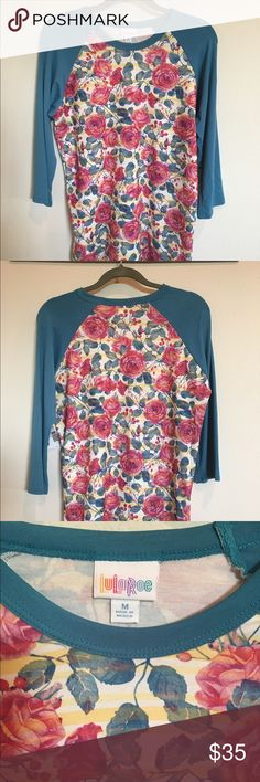 LulaRoe Randy Tee in Rose Print Brand new with Tags medium Randy Tee in a beautiful rose print with 3/4 length blue sleeves. I ordered it and changed my mind, but it's a beautiful shirt! LuLaRoe Tops Tees - Long Sleeve