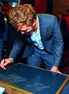 Robert Pattinson signing his name at the Handprint Ceremony