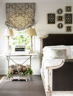 soft grey walls, framed collection above bed, patterned soft roman shade, double lamps on nightstand