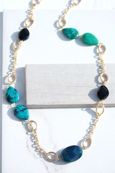Gold chain link necklace with green and black stone stations.