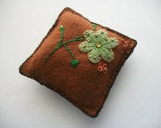For the cover of this needle book I choose dark green wool felt and decorated it with a lighter green Folk Art bird, hand embroidered felt flowers, little opaque sequin flowers and swirls. For the embroidery I used DMC cotton mouliné floss and DMC light green metallic thread. Little Japanese seed beads are the hearts of the flowers.  Closed the book measures 10 x 8 cm or about 3.9 x 3.1 inches. You will have 8 pages (4 sheets) to organize and store your needles and pins.  All of my needle…