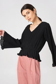 The Pleated Plunge Top by Boohoo and features a v-neck, long wide sleeves, a stretchy gathered waist, wavy edges, and a pleated design.
