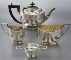 """3 Pc. English sterling silver tea service, incl.: a teapot, creamer and covered sugar; teapot with wood handle and finial, all with gadrooned lower half and engraved with a crest, Sheffield maker's mark """"FW"""" and marked for 1902. Together with a like strainer having contemporary English marks. 15.18 ozt. weighable. Teapot: 5.25''H x 11.25''W."""