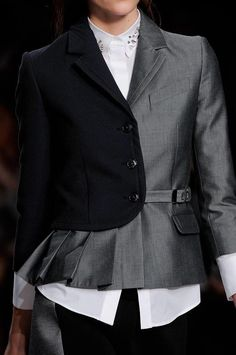 take 2 thrift jackets with buttons the align with each other..  Cut in half.  Use 1/2 of the base jacket and make pleats for top front as shown.  If your 2nd jacket is longer than the dark one shown here, you can cut it down to show the pleats you've made.  Stitch it all together.