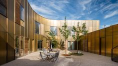 NORD Architects Copenhagen hospice features golden facades with curving cutouts that surround quiet courtyards.
