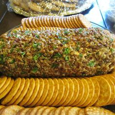 I just kinda made this one up, but it sure is tasty and goes over well at parties and holiday gatherings.  I use something I find at Krogers called pub cheese (sharp cheddar variety) but any cheddar cheese spread would work. You can make this into any shape you like such as a cheese ball instead of a log. At Halloween time I make it into a spider using pretzels for legs and pickled onion and black olives for eyes. Serve with whatever crackers you prefer and enjoy this pretty appetizer!