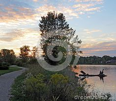 A winding path beside a small lake at sunset makes for a pleasant hike.