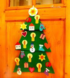 Za dveřmi jsou vánoce ... - adventní kalendář Adventní stromeček vytvořený z několika vrstev lepenky a silného papíru. Je polepený zeleným filcem. Stromeček je patrový, složený ze tří závěsných částí.Slouží jako nástěnka, kam je možné špendlíky připíchnout ozdůbky. Ozdoby - 24 ks, opatřených čísly, jsou z tuhého kartonu a barevných filců. Jednotlivá ...