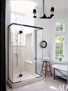 A bath features a vintage tub supported by a custom-made metal base; the 19th-century clock is from Lee Stanton Antiques, the shower fittings are by Waterworks, and the floor is paved with limestone.