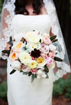 Amy Burke Designs created this eclectic wedding bouquet using garden roses, ranunculus, and cosmos in cream, pink, peach, and chocolate brown. Stems of natural...