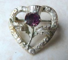 Vintage, dainty, Scottish, sterling silver heart and thistle brooch manufactured by Ward Brothers. The brooch is formed from a silver heart delicately engraved with Scottish roses. The center of the brooches heart is set with a Scottish thistle with a faux amethyst stone.