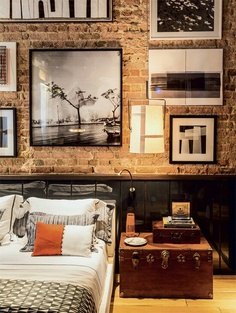 This loft bedroom features black wainscoting, exposed brick, a large trunk used as a nightstand and a gallery of prints. A modern, urban space.....V