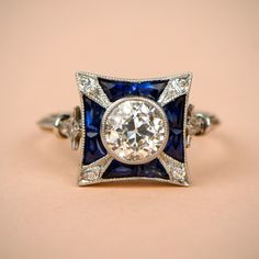 A stunning Diamond and Sapphire Engagement Ring, adorned on the shoulders by a fluer-de-lis and triple wire band.