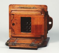 c. 1880, Gem Apparatus Camera by J. Lancaster & Son, England. Ferrotype plate. 12-lens camera taking 12 exposures on a 9 x 12 cm ferrotype plate. Polished mahogany body. Front panel slid sideways to uncover lenses and back again to end the exposure.