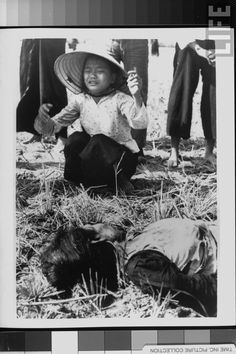 Grieving young woman kneeling as she weeps over body of one of fifteen civilians who were killed in explosion of homemade Viet Cong mine on country road where most of victims were riding in Lambretta Tricycle which struck mine during Vietnam War. Location:	Tuy Hoa, Vietnam Date taken:	1966