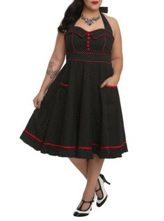 Black dress with white polka dots, red trim, five red buttons on center front of bodice and two pockets.