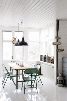 turquoise folding chairs. wooden table top with metal legs. oversized window ledge. lighting. white gloss floors. white paneled ceiling.