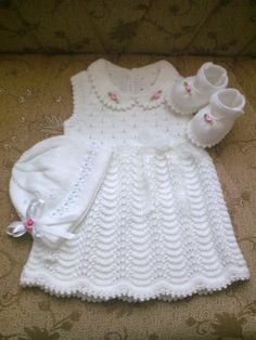 Same little white dress as before, only now the lace pattern on the skirt is Old Shell, and little ribbon roses have been added to embellish matching hat and bootees. ~~ Örgü bebek elbisesi ayakkabısı ve şapka takımı Crochet Baby Dress Pattern, Baby Dress Patterns, Baby Knitting Patterns, Girls Knitted Dress, Knit Baby Dress, Knitted Baby, Smock Dress, Knitting For Kids, Crochet For Kids