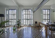 Splendide piastrelle in ceramica dipinta con pattern geometrici per il living a pianta aperta dell'appartamento The VVall. A ristrutturarlo lo studio catalano Nook Architects in un edificio di inizio Novecento a Barcellona