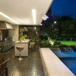 Área de lazer em casa, com piscina e churrasqueira, acabamentos atuais e elegantes.ProjetoAngela Borsoi e Sônia Lacombe.