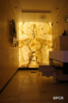 Backlit Onyx feature wall in bathroom or small space.  Onyx is a translucent stone and transforms light to a warm ethereal glow.
