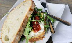 Sandwich van B'rustiek bruin, belegd met buratte, een luxe mozzarella, met serranoham, huisgemaakte pesto, zongedroogde tomaatjes, rucola en pijnboompitjes.