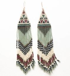 """These extra long brick stitch earrings hang at 7"""". They are made with rust, bronze, sea foam, navy, and dark green seed beads."""
