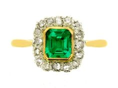 Antique emerald and diamond cluster ring, English, circa 1850. A gold and silver ring set with one central rectangular emerald-cut old mine emerald in a gold rubover collet setting with an approximate weight of 0.70 carats, encircled by a conforming single row of sixteen round rose cut diamonds in silver cut down settings with an approximate total weight of 0.30 carats, flanked by inward tapered shoulders, and on a D-shaped gold shank.