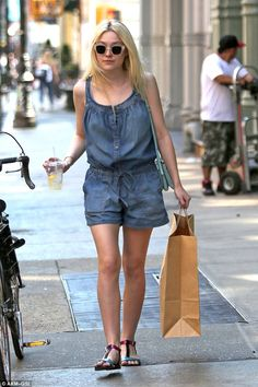 Short story: Dakota Fanning looks lovely in a denim jumpsuit and metallic sandals as she takes a shopping trip in NYC on Monday