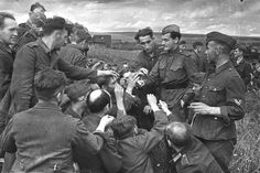 A Soviet soldier shares his cigarettes with German prisoners. [World War II, July, 1943]