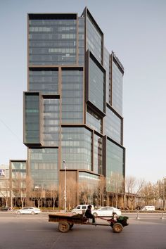 Shanghai studio Neri&Hu has completed its largest project to date – a total exterior and interior overhaul of a hotel in Zhengzhou, China, featuring a new facade resembling a pile of glass boxes and an entrance surrounded by a forest of bronze columns.