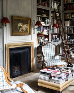 Wonderful library with fireplace, blue check chairs and fab gray-washed paneling.