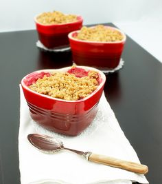 A photo of a Pear, Rhubarb and Raspberry Fruit Crumble dessert in a red, heart-shaped ramekin placed on a white napkin with a dessert spoon ...