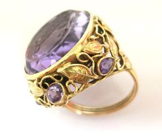 Arts and Crafts Amethyst Intaglio Ring in a Unique 14K Mounting  A classic figure carved into a large amethyst is the highlight of this very special ring. The gold work (14K tested and guaranteed ) is enhanced by five small amethysts. The leaf design on the mounting is indicative of the arts and crafts creations.