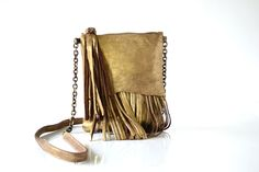 Small, zip top cross body bag. Unique signature raw edged flap, gives way to a flowing mix of fringe and chain. Beautiful long tassel zipper pull featuring twisted metal motif adornment.