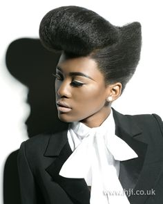 Afro hair was styled into a slightly pointed chignon, with a front section left loose. This front panel was then wrapped up to create a rounded quiff.