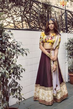 Yellow floral blouse with shoulder cut-outs and shoulder strap, burgundy silk skirt with borders, blush soft net dupatta.