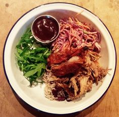 8 hour slow roast pulled pork with BBQ rub (salt, brown sugar, onion powder, garlic powder, pepper, paprika, all spice, mustard, thyme) with red slaw (red onion, red cabbage, carrot, scallion, Mayo, herb dressing), rocket, crackling & BBQ sauce.