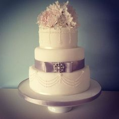 The Gatsby theme is going to be big news this year, and festoons of pearls, luxurious satin ribbons and exquisite brooches are synonymous with this era. The cake is adorned with blush peonies, simple white roses and hydrangea blossoms.  www.theprettycakecompany.com