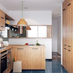 A small kitchen with pretty wood storage and deep blue tiled floors has everything a home chef would need. Except maybe excess counter space.